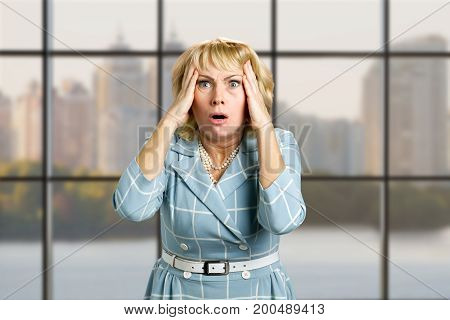 Portrait of astonished mature woman. Closeup portrait of a terrified white-skin woman looking shocked surprised in full disbelief hands on head, office window background.