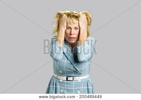 Desperate mature woman on grey background. Depressed businesswoman with closed eyes pulling her hair on grey background.