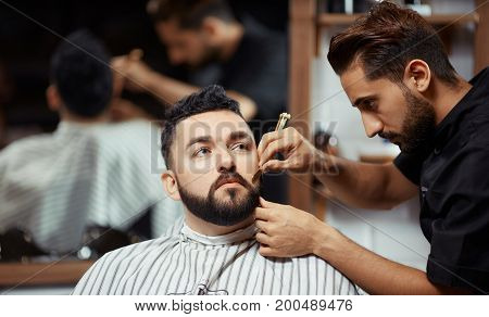 Young man shaving client sitting in chair in barbershop.
