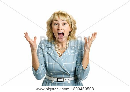 Excited mature lady, white background. Surprised happy white-skin woman looking straight with open mouth and raised hands in excitement.