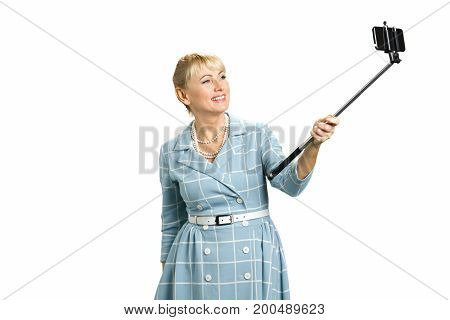 Happy mature woman taking selfie. Beautiful white-skin lady taking a photo with selfie stick isolated on white background.
