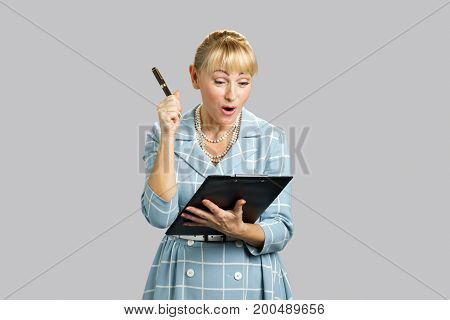 Surprised woman looking on clipboard. Excited mature lady looking surprised with clipboard isolated on grey background.