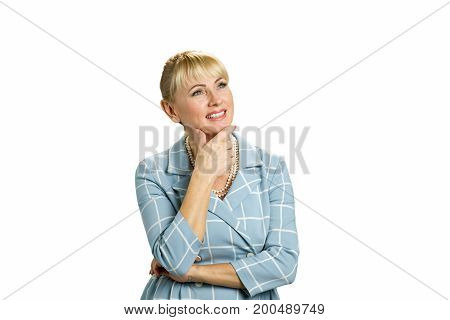 Mature woman smiling on white background. Middle aged woman holding her hand under chin and looking upwards smiling isolated on white background.
