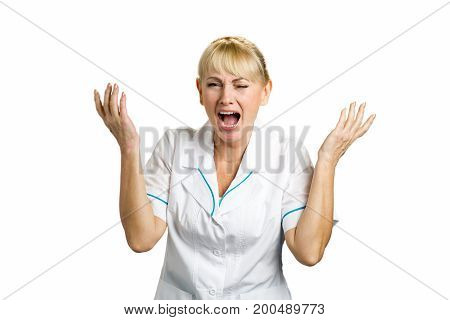 Screaming medical worker on white. Frustrated and shocked mature nurse with raised hands and open mouth standing on white background.