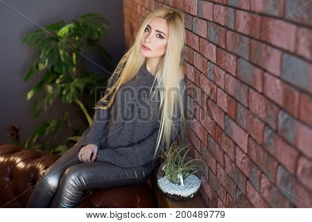 Attractive Blonde Young Woman Sitting Near Brick Wall And Think. Girl In Beautiful Room Interior
