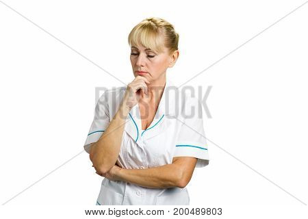 Confident thinking mature female doctor. Portrait of thoughtful mature medical female doctor holding chin on hand and thinking on white background.