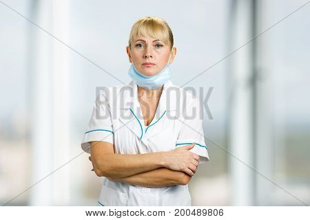 Portrait of nurse with medical mask. Serious mature medical doctor standing with medical mask under chin on blurred background.