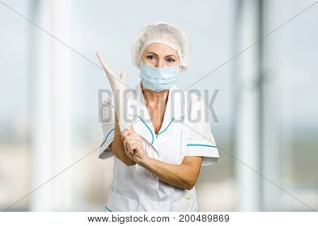 Female surgeon putting on a glove. Female medicine doctor in protective mask and cap putting on white protective glove, blurred background.
