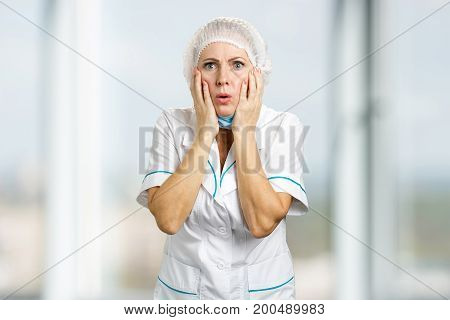 Mature female doctor looking shocked. Surprised mature nurse holding hands on face and looking worried, blurred background.