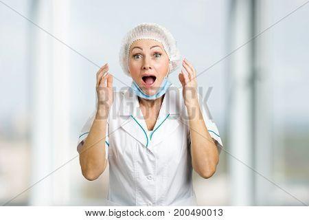 Happy mature female doctor. Excited white-skin nurse with open mouth and raised hands. Human facial expressions.