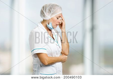 Depressed unhappy white-skin female doctor. Upset mature female doctor holding hand near head on blurred background, side profile.