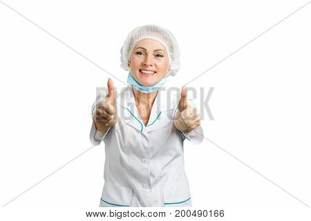 Cheerful doctor raised thumbs up. Professional and smiling female doctor with thumbs up over white background.