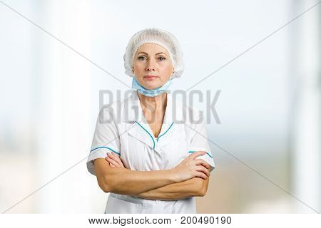 Female surgeon with crossed arms. Portrait of confident mature medical doctor in white uniform.
