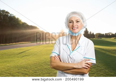Smiling female surgeon crossed arms. Happy female surgeon standing arms crossed on nature background.