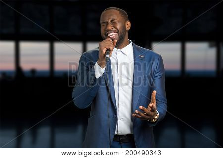 Singing man on the evening background. Darkskinned man with microphone. Black man is singing with closed eyes and passion.