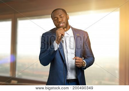 Jazzman singing on sunlight background. Beautiful perfomance of black arist. Talanted afro american jazz singer.