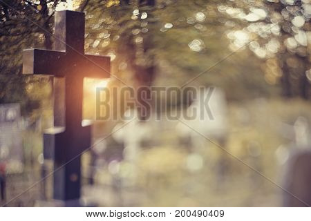Blurry background with a cross on a grave behind a fencing. It is photographed in the Free-Lensing equipment.