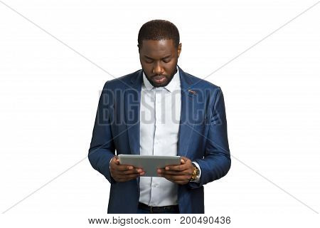 Serious businessman using computer tablet. Afro american executive director with electronic pc gadget on white background.