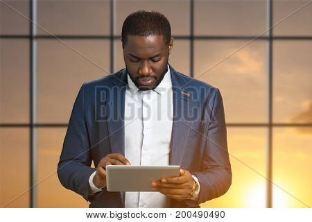 Successful businessman on sunlight background. Young project manager with computer tablet in hands.