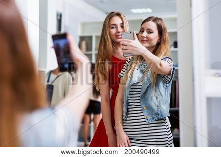 Two smiling girls taking selfie while shopping in a clothing store.