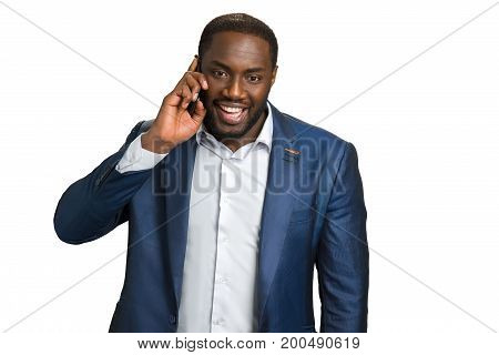 Cheerful businessman speaking on phone. Happy black manager with mobile phone on white background.