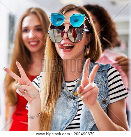 Two girlfriends having fun while doing shopping making faces in the mirror showing V-sign wearing three pair of sunglasses at the same time in womenswear store.