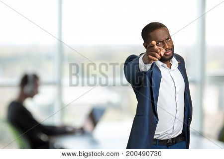 Serious businessman pointing forward. Black man in suit pointing forward with his forefinger. Angry afro american businessman showing index finger.