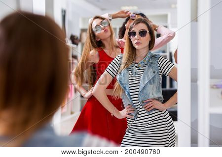 Glamorous girls trying on sunglasses posing in front of the mirror in fashion boutique.