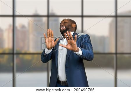 Business man put his hands forward. Black manager with emotion of fear on blurred background. Surprised and scared businessman.