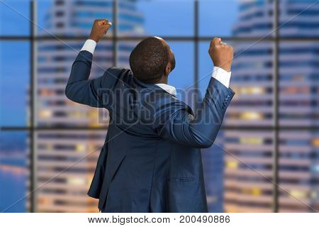 Rear view of successful businessman. Back view of happy afro american manager on skyscraper background. Excited executive raising fists on evening city background.