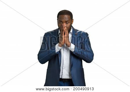 Frustrated young businessman with clasped hands. Man in formalwear holding hands clasped near mouth. In searching of solution.