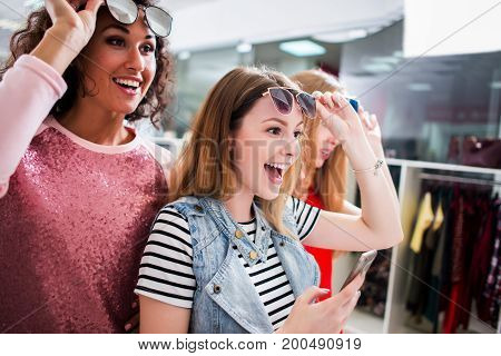 High-angle shot of young stylish female friends wearing trendy sunglasses and clothes having fun in shopping center.