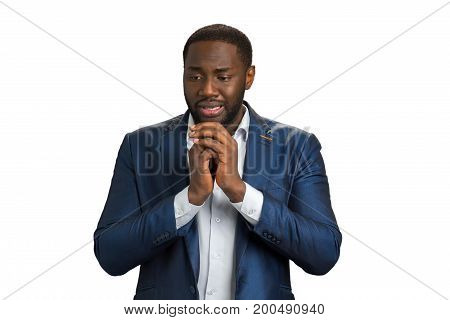 Businessman deep in despair and emotional distress. Afro american young man in formal wear holding hands near face and crying. Deep human expression of problem.
