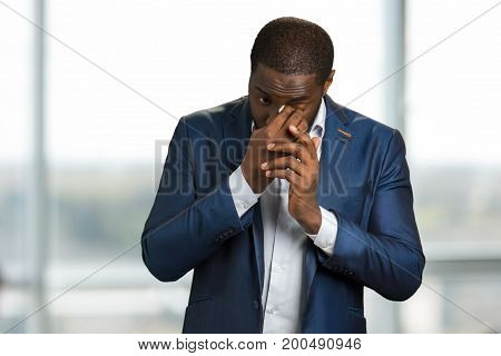 Crying businessman wiping his tears. Black man in formal wear crying and wipe his eyes with white napkin.