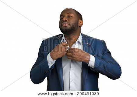 Afro american businessman unbutton shirt. Handsome young manager with sexual look unbutton his shirt. Successful businessman is opening expensive white shirt.