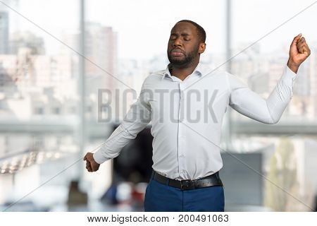 Sleepy businessman stretching in office. Young man stretched out his arms wide on blurred background. Afro american manager starts day in office with morning exercises.