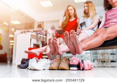 Young smiling girlfriends sitting in a clothing store looking at their bare feet and pile of new shoes and laughing.