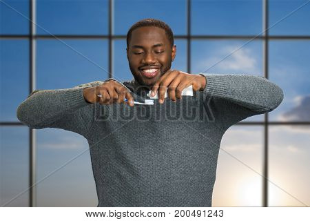 Black man applying toothpaste on a toothbrush. Smiling afro american man with toothpaste and brush on blue sky background. With care of the oral health.