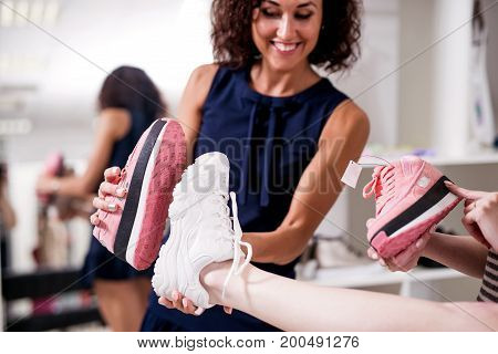 Young women helping their friend to choose sports footwear comparing the soles of new and old shoes in fashion showroom.