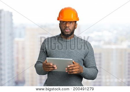Man in safety helmet and computer tablet. Builder man working with a tablet in a protective helmet. Engineer in safety helmet conducting inspection with tablet.