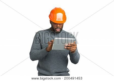 Man in helmet working on tablet. Project manager in orange protective helmet using computer tablet on white background.
