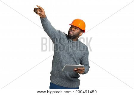 Construction supervisor on white background. Young architect in orange helmet control building process and pointing with finger upwards. Black young engineer holding computer tablet.