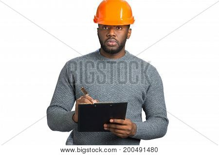 Confident engineer writing on clipboard. Contractor with hardhat and clipboard isolated on white background.