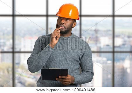 Architect holding hand near chin. Thougtful engineer with protective helmet and clipboard on blurred background.