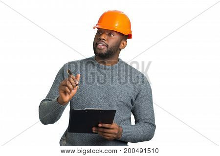 Young engineer inspecting construction. Handsome afro american architect with clipboard close up. Attractive project manager with helmet and clipboard on white background.