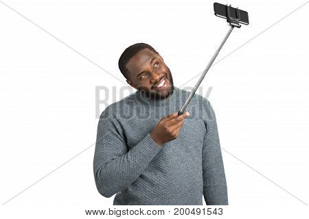 Handsome man taking photo with selfie stick. Beard afro american smiling guy taking picture with phone on monopod. Positive man in grey sweater with monopod on white background.