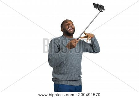 Young man taking selfie picture in studio. Studio shot of young happy black afro american man smiling and gesturng while taking selfie picture.Positive black man with monopod on white background.