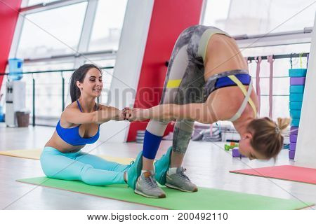 Two smiling young Caucasian girlfriends doing stretching exercise together in fitness club.