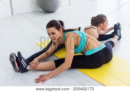 Two slim girls taking part in yoga class working in pair doing partner side seated wide angle pose called parsva upavistha konasana in sports center.