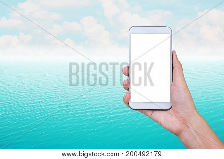 Woman's hand holding smart phone with ocean water background